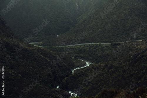 Foto op Canvas Grijze traf. Paisaje montañoso en un día gris y oscuro con un río y una carretera atravesando la imagen