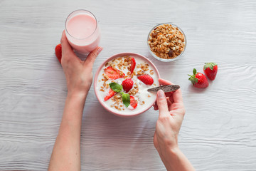 Woman's hands as she eats healthy breakfast .Yogurt with strawberries and granola in a bowl on the table.Top view
