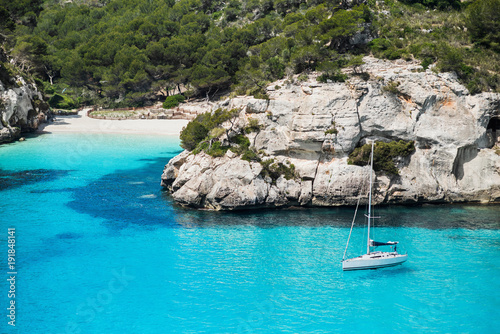 Fotobehang Zeilen Beautiful bay in Mediterranean sea with sailing boat, Menorca island, Spain. Yachting, travel and active lifestyle concept