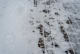 In winter, a snow-covered paving block in the city. Footprints from boots in the snow. Sidewalk in the winter in the snow. - 191855571