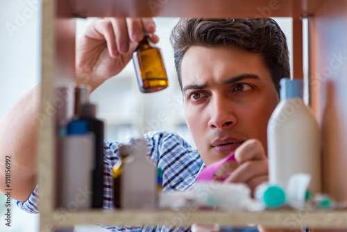 Staande foto Apotheek Sick ill man looking for medicines at farmacy shelf
