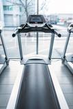 Treadmill against big window, gym interior, nobody