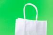 Leinwandbild Motiv white shopping bags on green background