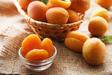 Sweet apricots in basket and bowl on sackcloth - 191860163