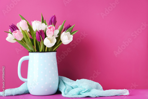 Bouquet of tulips in jug on pink background