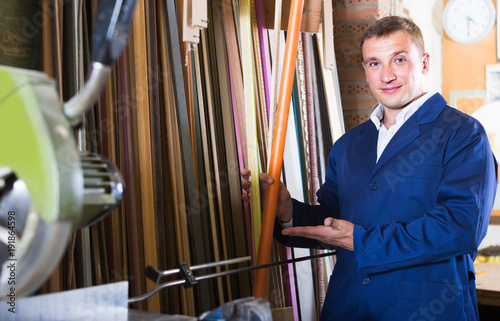portrait of man in uniform choosing framing moulding in studio
