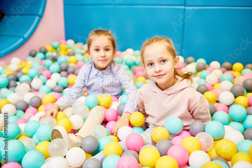 Two cute little girls looking at camera while sitting among colorful balloons in theme park