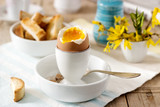 Breakfast from soft-boiled egg, bread toast, coffee with cream and fresh newspaper. - 191869129