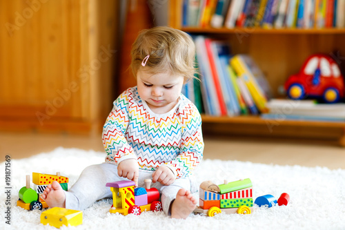 Adorable cute beautiful little baby girl playing with educational wooden toys at home or nursery. Toddler with colorful train