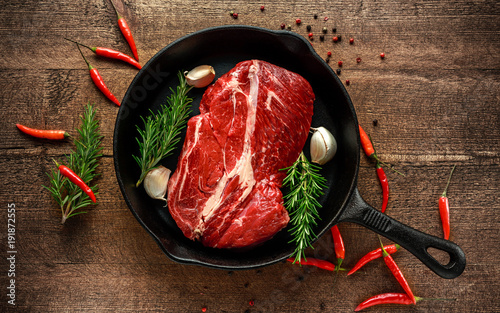 In de dag Steakhouse Fresh Raw braising steak in rustic skillet with rosemary, chilli and garlic