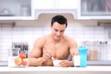 Handsome muscular young man having healthy breakfast in kitchen - 191876962