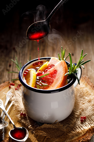 Hot Tea infusion with rosemary, grapefruit, lemon, red pepper and raspberry juice in an enamel mug on a wooden background