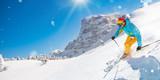 Skier on piste running downhill in beautiful Alpine landscape. Blue sky on background. - 191880125