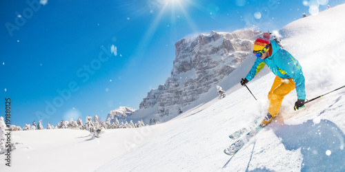 Skier on piste running downhill in beautiful Alpine landscape. Blue sky on background.
