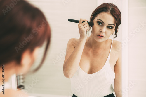 Serious young woman powdering face at mirror