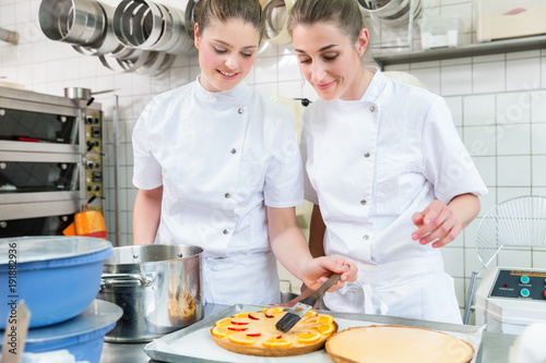 Women putting fruit on cakes in pastry bakery for later sale