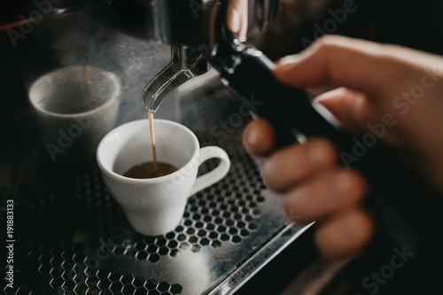 Prepare making hot coffee espresso in white glass cup at coffee machine