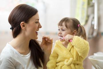 mother teaching daughter child teeth brushing in bathroom © Oksana Kuzmina