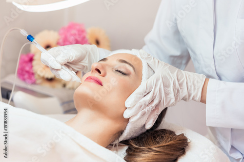 Beautiful woman relaxing during non-invasive facial treatment for rejuvenation in a contemporary beauty center with innovative equipment - 191883954