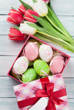 Easter eggs in gift box and colorful tulips