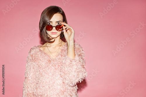 stylowy model kobiece w różowy sweter na różowym tle