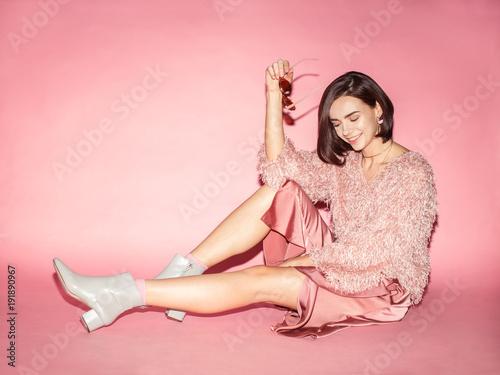 modelka kobieta w różowe okulary, sweter i spódnica siedzi na różowym tle