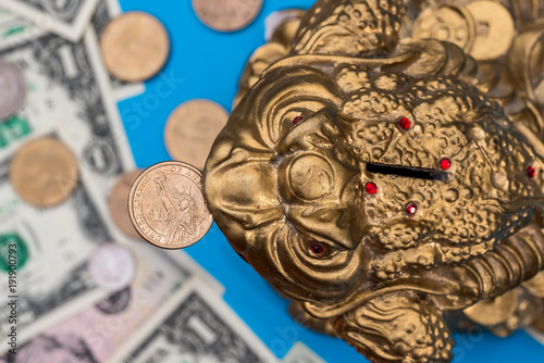 Fotobehang Kikker Symbol toad and dollar coin and banknote isolated on blue