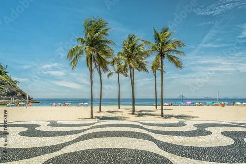 Fotobehang Rio de Janeiro Palms on Copacabana Beach and landmark mosaic in Rio de Janeiro, Brazil. Sunny day with blue sky