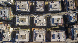Perpendicular aerial view of a group of buildings in the Tuscolana district in Rome, Italy. All the roofs are walkable and full of antennas and TV dishes. down the streets lit by the sun. - 191906923
