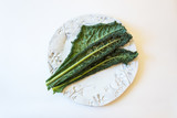 Green Italian lacinato Nero di Toscana heirloom Tuscan dinosaur kale on white plate, isolated on white, horizontal aspect