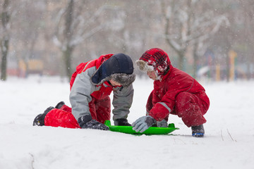 Two happy boys playing with slide on snowy landscape