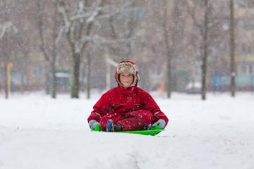 Smiling boy sitting at slide on snowy landscape