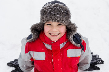 Adorable smiling boy sitting on the snow
