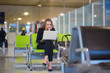 Woman in international airport working on laptop