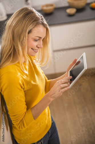 Attractive woman in home kitchen, using a digital tablet