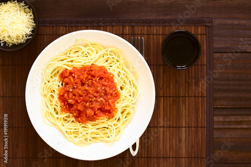 Wall mural Traditional Italian Spaghetti alla Marinara (spaghetti with tomato sauce) in bowl with red wine and grated cheese on the side, photographed overhead on dark wood with natural light
