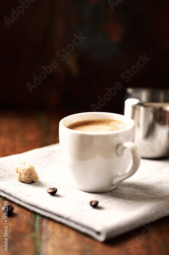 Cup of Cafe Crema and Milk Jug on rustic wooden Background