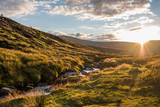 Beautiful, cloudy sunset over a small river flowing through green, grass covered hills in Wicklow Mountains, Ireland - 191926970