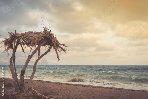 Fotobehang Beige Palm tree, bungalow against the blue stormy sea at sunset