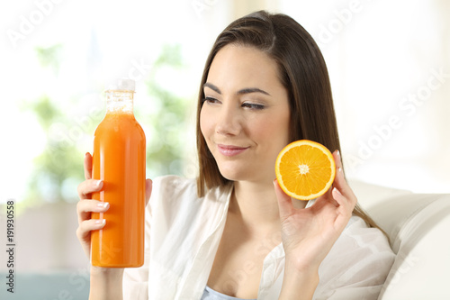 Woman showing an orange and a juice bottle