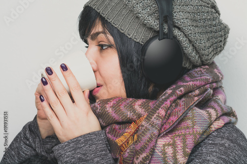 Attractive woman wearing winter clothes and drinking hot tea