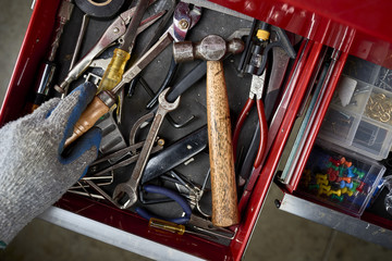a man opening a tool drawer and holding a chisel inside a workshop.