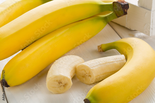 Bundle of fresh, ripe, yellow bananas with sliced banana pieces on table - 191937121