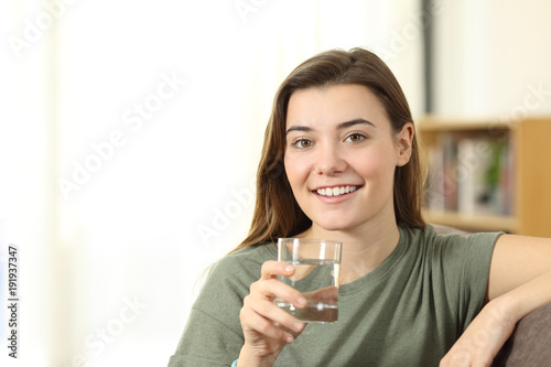 Happy teen holding a glass of water looking at you