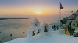 sunset shot of a greek flag and church bells at oia on the island of santorini, greece - 191939520