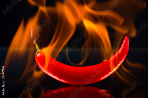 Foto op Canvas Hot chili peppers Burning hot chili pepper in flame on a dark, black background. Fiery pepper.