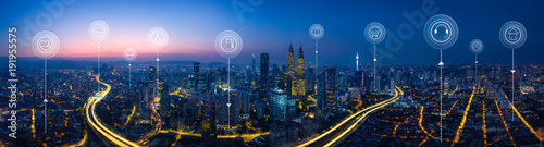 Leinwanddruck Bild Panorama aerial view in the  cityscape skyline  with smart services and icons, internet of things, networks and augmented reality concept , early morning sunrise scene .