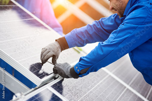 Leinwanddruck Bild Smiling male technician in blue suit installing photovoltaic blue solar modules with screw. Man electrician panel sun sustainable resources renewable energy source alternative innovation