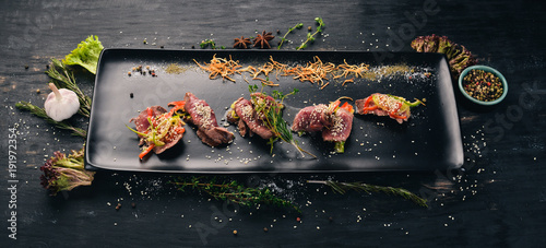 Foto op Canvas Steakhouse Grill Steak with cucumber, paprika and garlic. Cold snacks. Top view. On a black wooden background. Copy space.