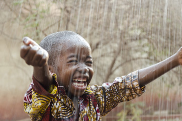 Little Native African Boy Standing Outdoors Under the Rain (Water for Africa Symbol)